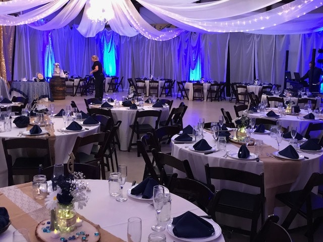 indoor wedding reception set up with white tables, black chairs and napkins, and white curtains draped from ceiling