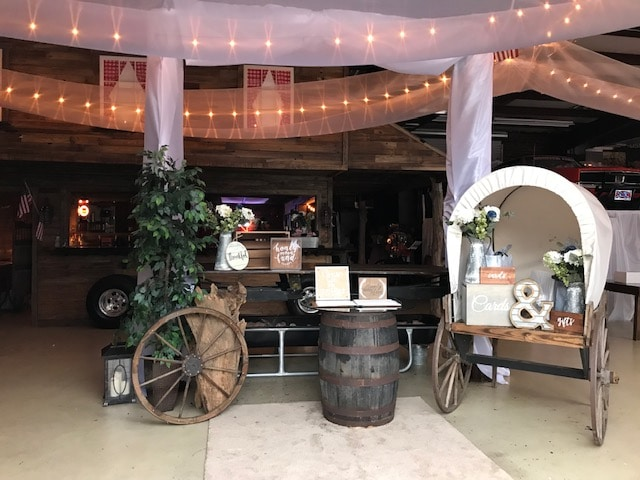 small covered wagon, barrel, and other rustic items set up as entry area to barn wedding