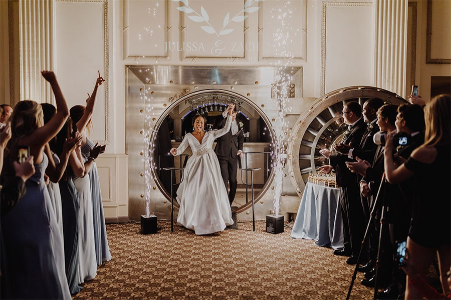 bride and groom coming out of a vault with sparks literally flying around them as their guests cheer.