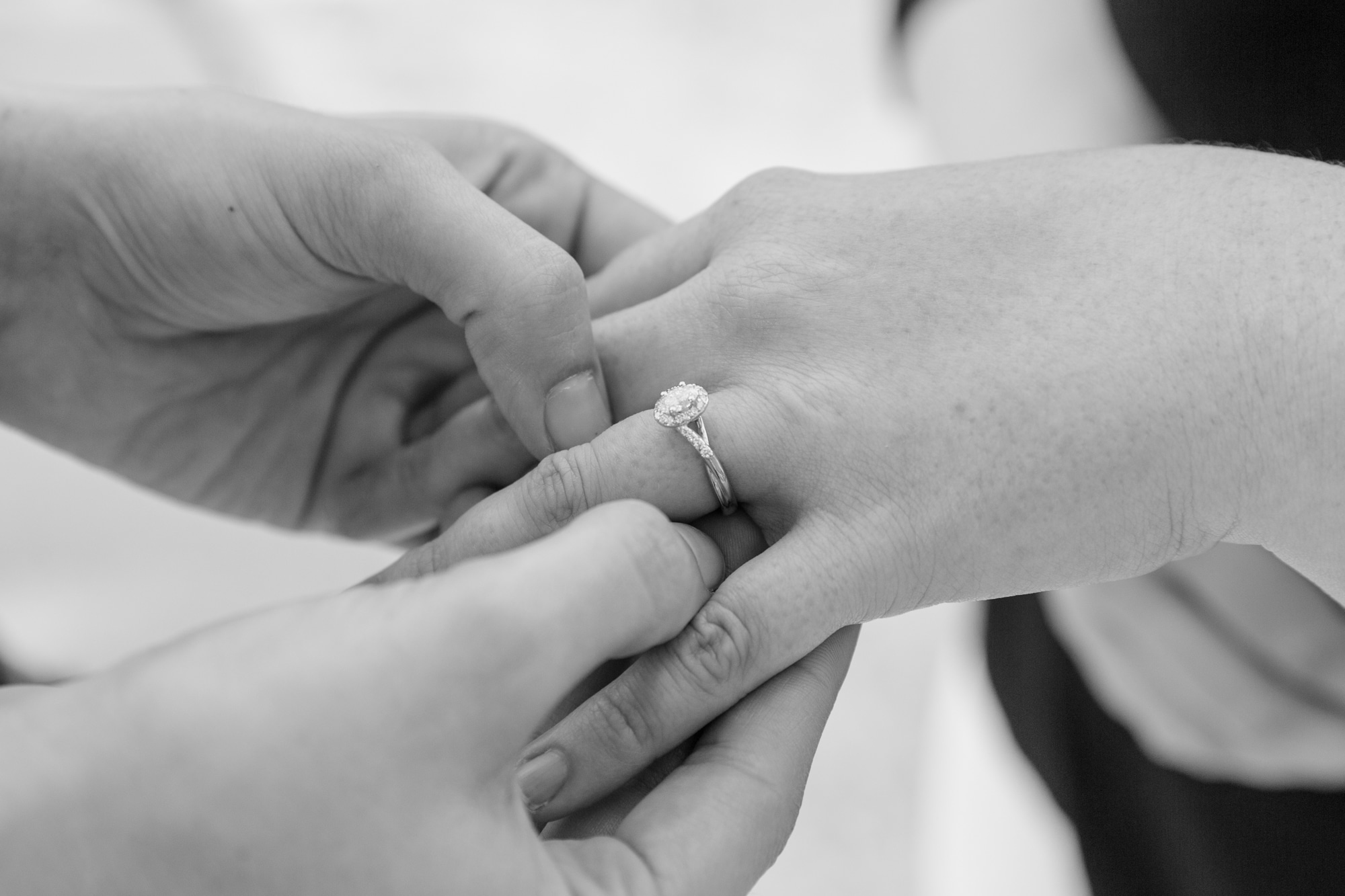 black and white image of man holding woman's hand with engagement ring on