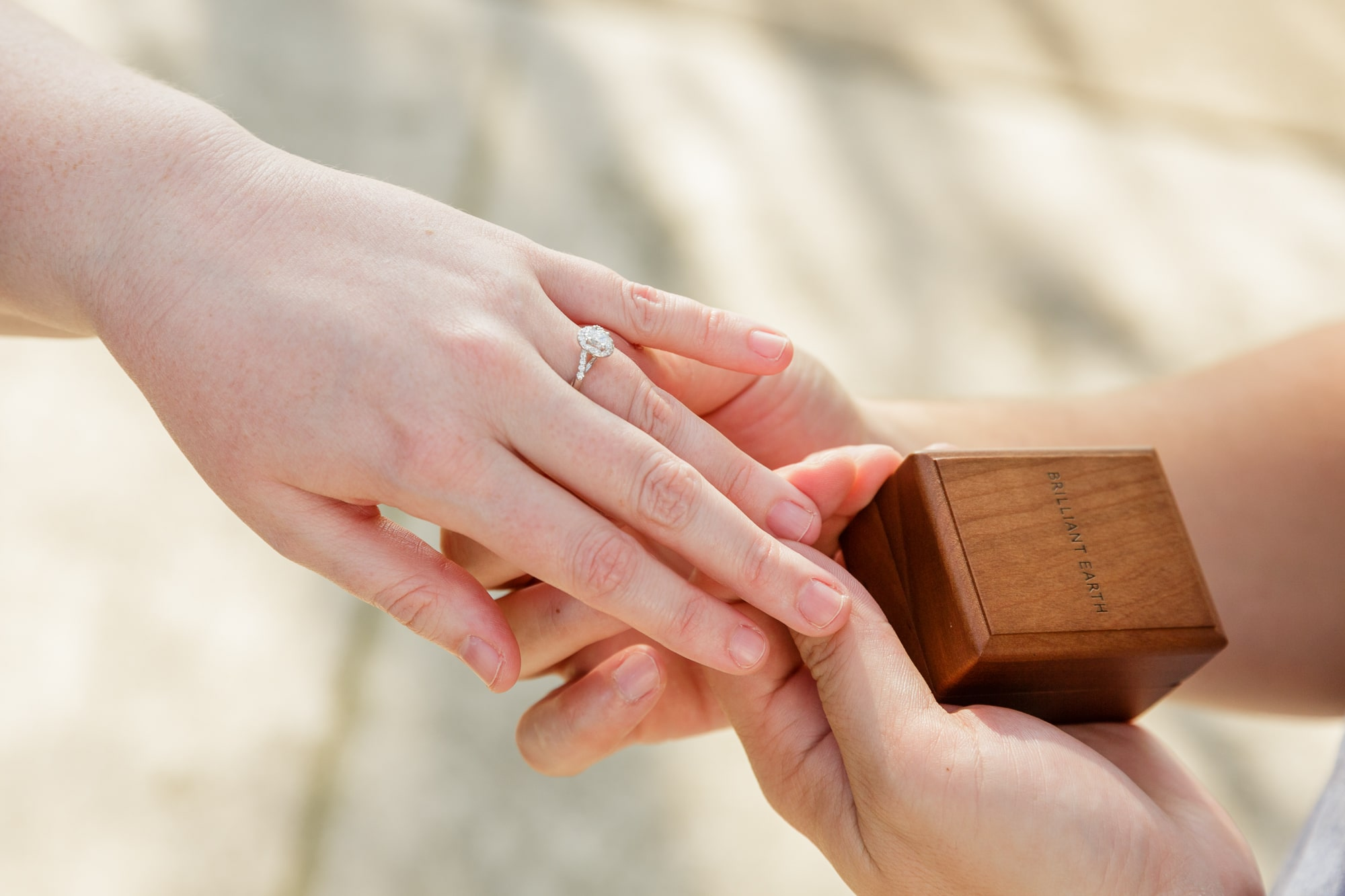 man holds fiances hand with new engagement ring on it while holding the wooden ring box it came in as well