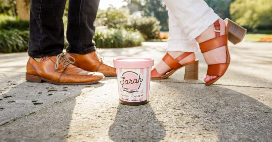 close up picture of couples feet with shoes on outside and a homemade proposal prop of a kelly's homemade ice cream container