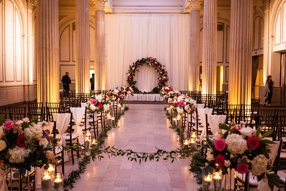 inside area for wedding ceremony at the treasury on the plaza decorated with matching white and pink flowers
