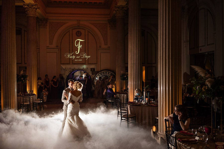 bride and groom kissing during first dance at wedding reception as fog fills the dancefloor