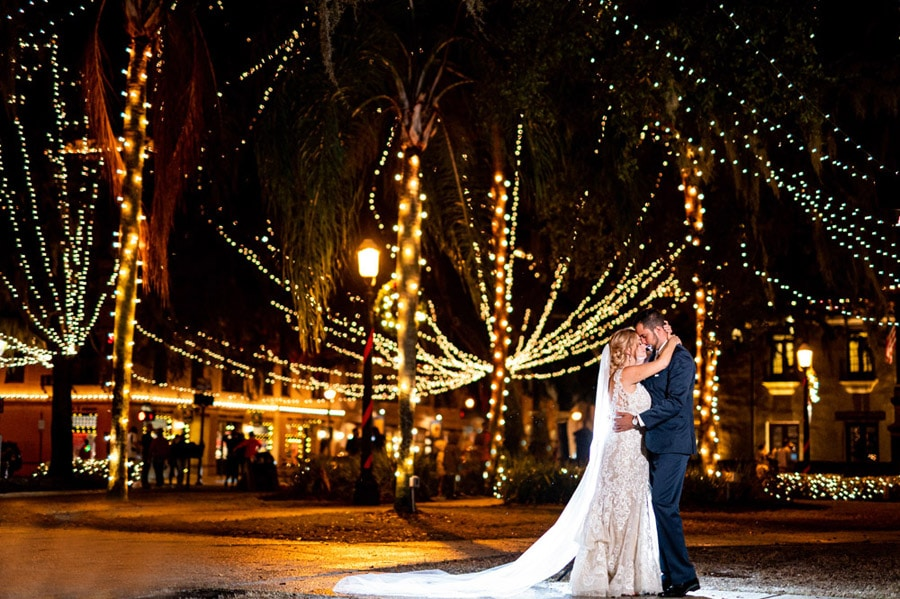 bride and groom dancing in the spotlight at night outside in an area where all the trees are lit with lights and market lighting is everywhere