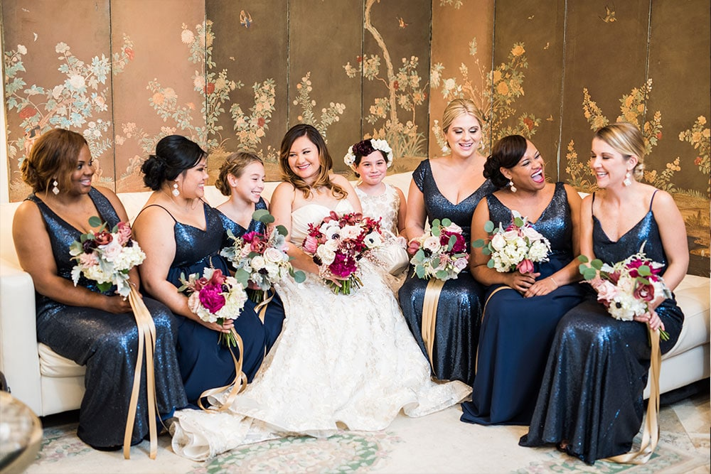 bride sitting on the couch with all of her bridesmaids all holding their bouquets