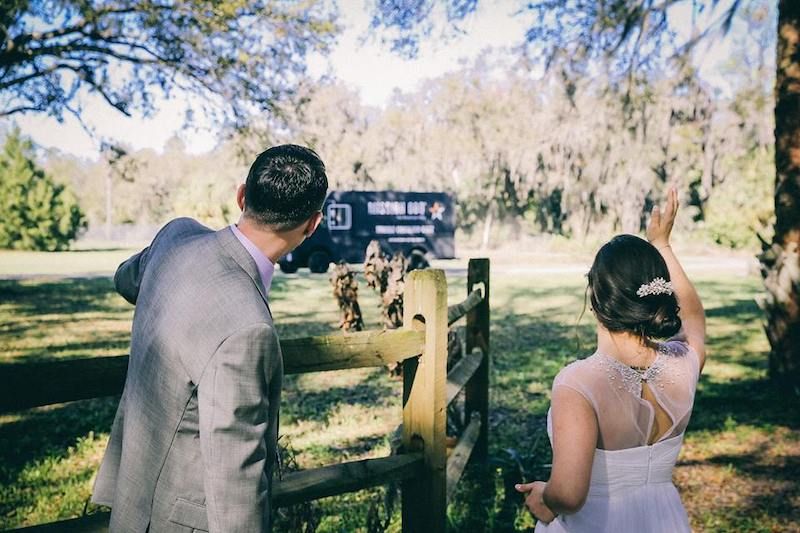 bride and groom waving at Mission BBQ catering truck as it pulls onto farm for the wedding buffet