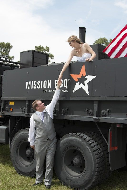 bride standing in the back of the Mission BBQ truck holding hands with groom who is standing next to the truck
