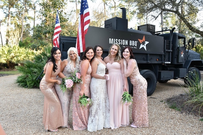 bride and her bridesmaids standing in front of Mission BBQ truck with two American flags on the back of it