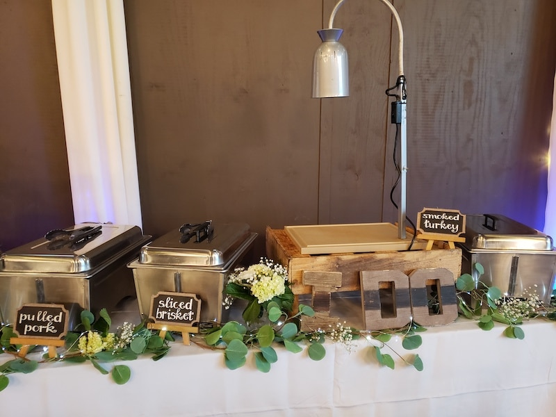 wedding buffet line from Mission BBQ decorated with flowers and wooden I Do sign