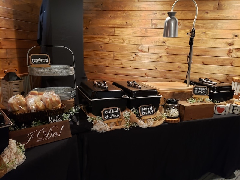 wedding buffet setup from Mission BBQ for rustic country wedding with buffet line decorated with flowers and signs
