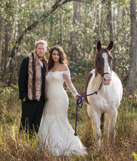 bride and groom with horse in woods