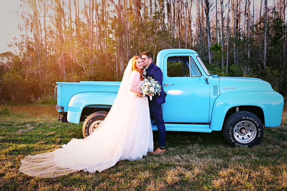 couple in front of ol' blue pickup truck