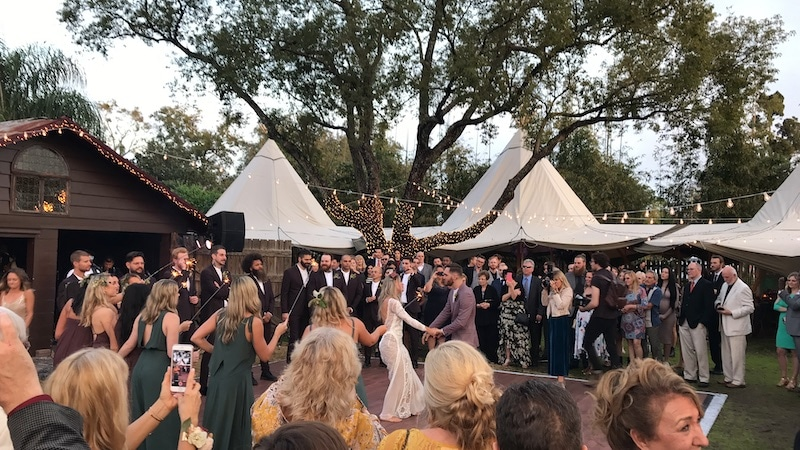bride and groom dance while guests cheer