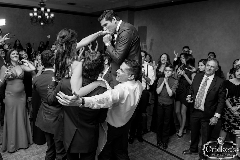 groom kisses the back of his wifes hands while their friends and family lift them up