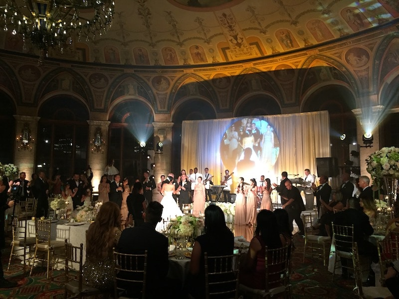 spotlight on the bride and groom as they dance in front of Paradigm Party Band
