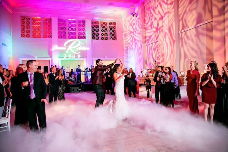 bride and groom dancing on fog covered dance floor while Paradigm Party Band plays and guests cheer
