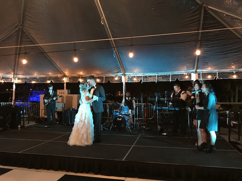 bride and groom dancing on stage while Paradigm Party Band performs