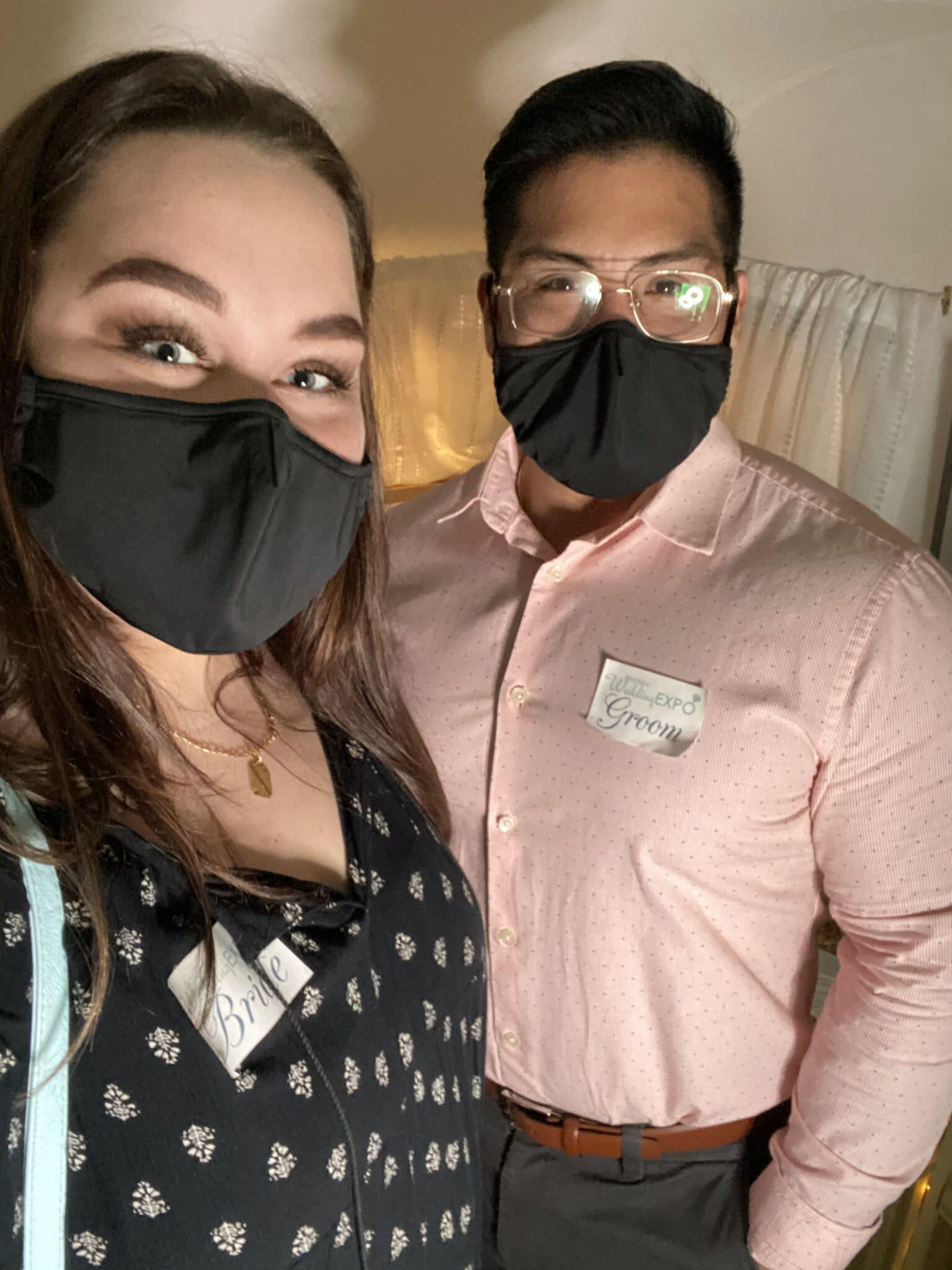 engaged couple standing with each other with black masks covering their faces and stickers that read bride and groom at wedding show
