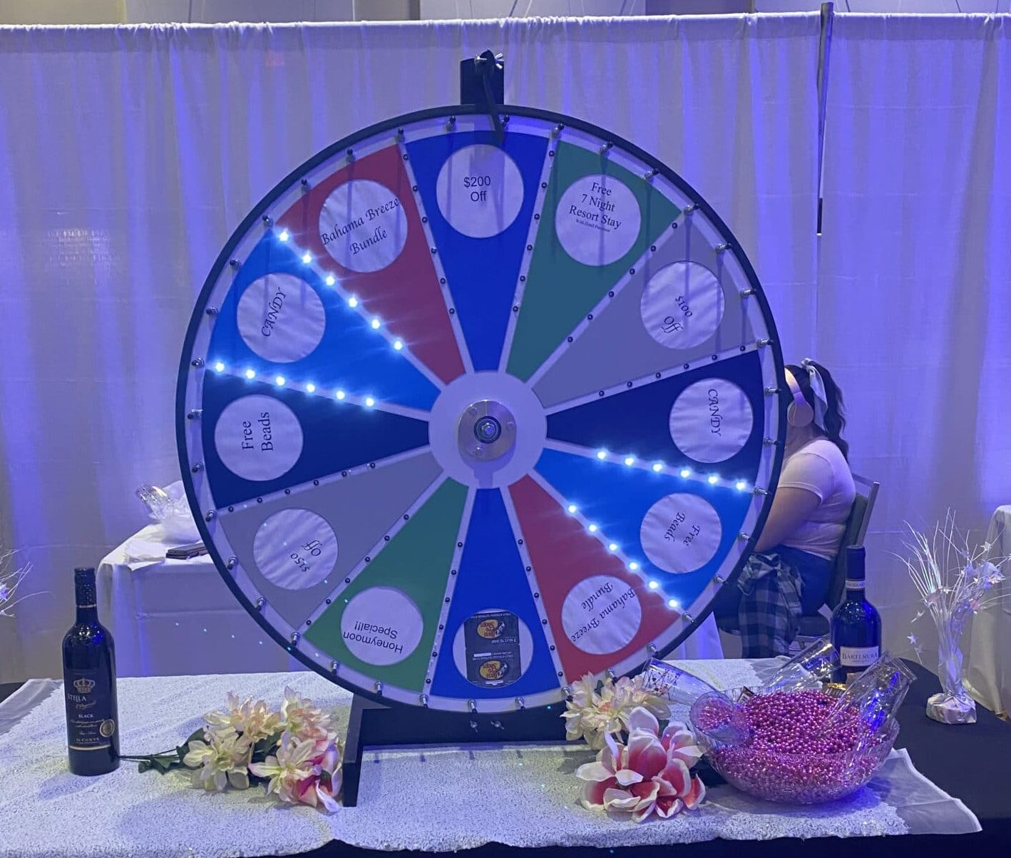 prize wheel with lights and different colored wedges with prizes on it sitting on top of a table