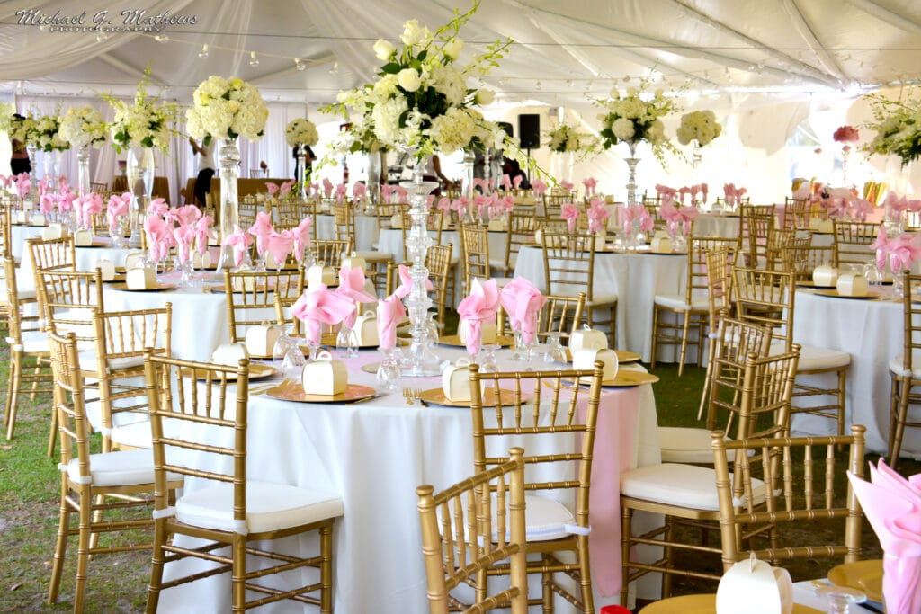 tented outdoor wedding reception with white tables, gold chairs, pink napkins, and tall yellow floral arrangements