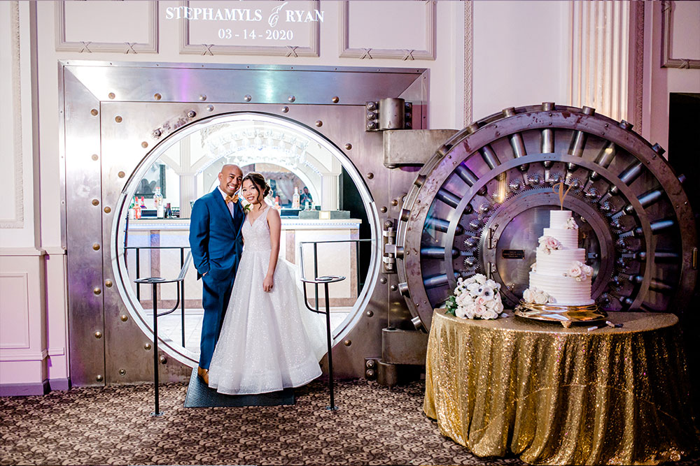 bride and groom standing at entrance of the vault standing next to their wedding cake