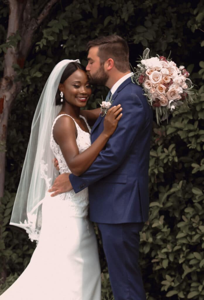 groom kissing bride outside under tree