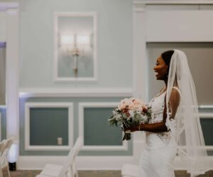 bride laughing while walking down the aisle at her wedding at the BEV Event Center