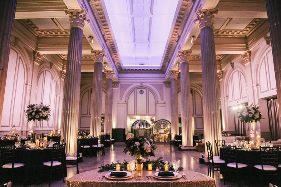 reception area setup at the treasury on the plaza with tables decorated with black linens and matching gold accent pieces