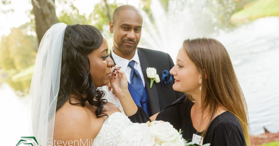 bride standing in front of groom with woman wiping tears from her face smiling while she holds her bouquet with a waterfountain pond in the background