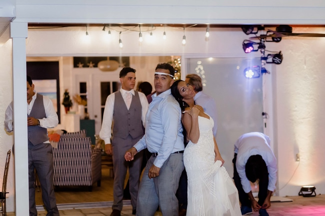 newly wed couple dancing back to back at wedding with some guests behind them and spotlights off to the side