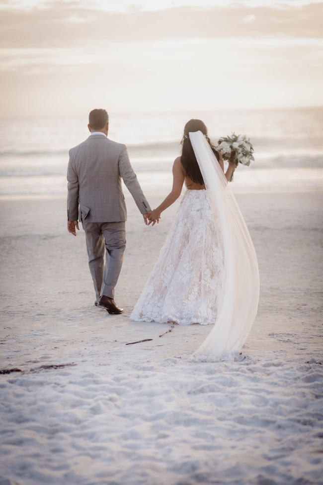 bride and groom holding hands and bride holds bouquet off to the right side on the beach