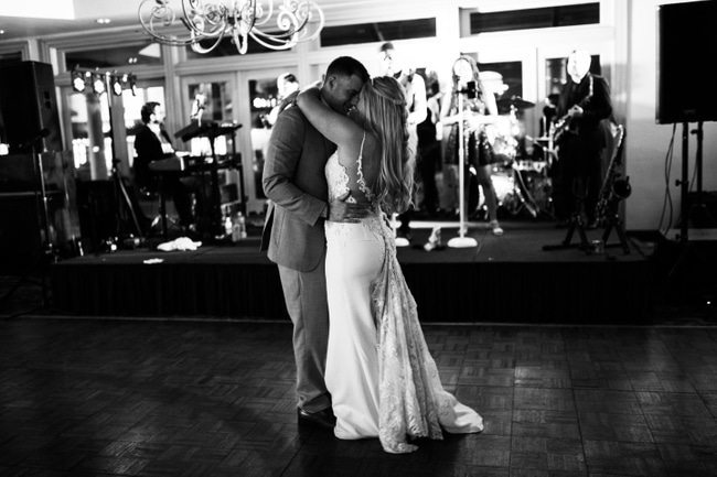 bride and groom share dance on the dance flor at wedding under chandelier in black and white image