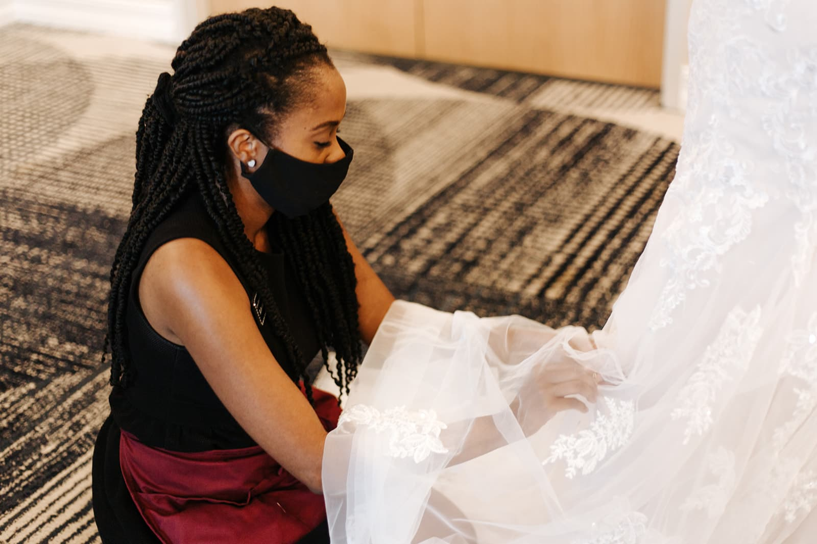 wedding planner crouches down near floor to gather the back of brides wedding gown and bustle it up while wearing face covering