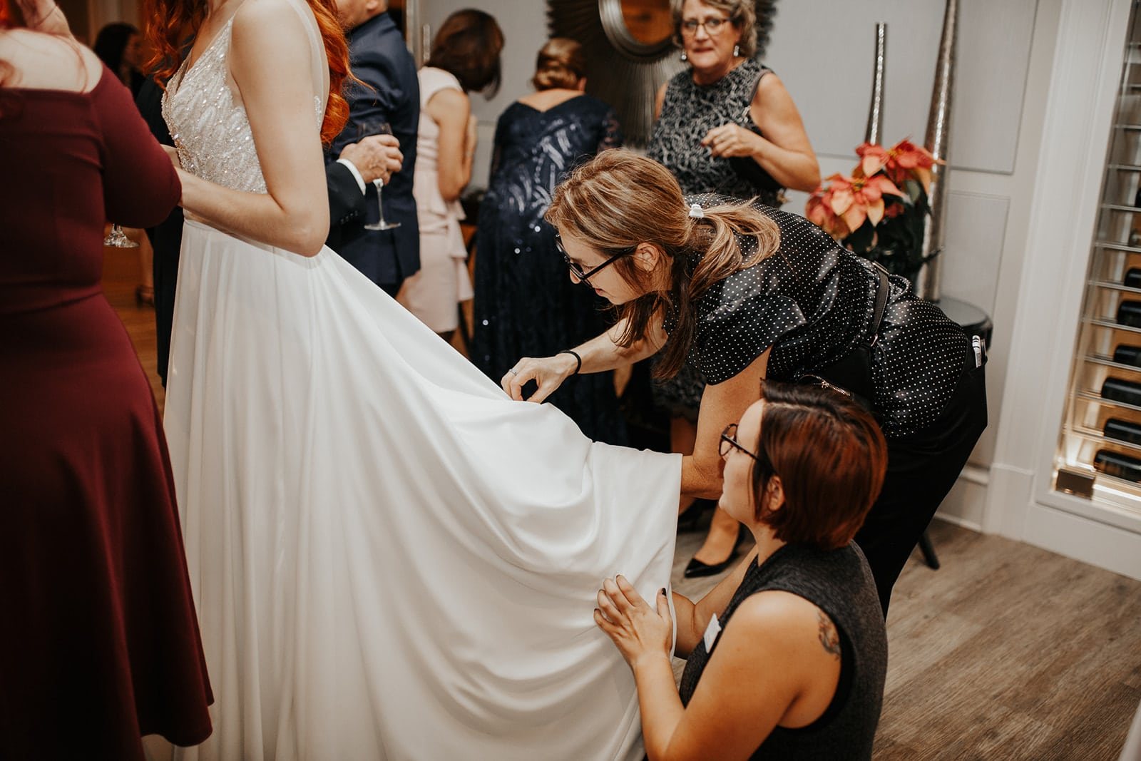 wedding planner gathers bridal gown during wedding to bustle it up for easier walking