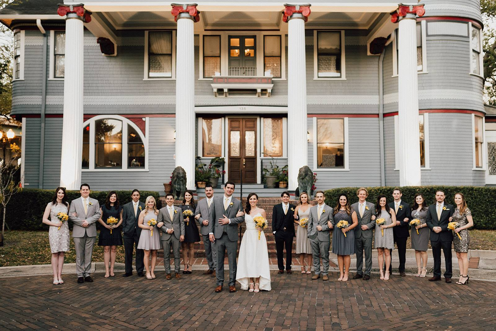 big wedding party on either side of bride and groom in front of big mansion with four tall white columns