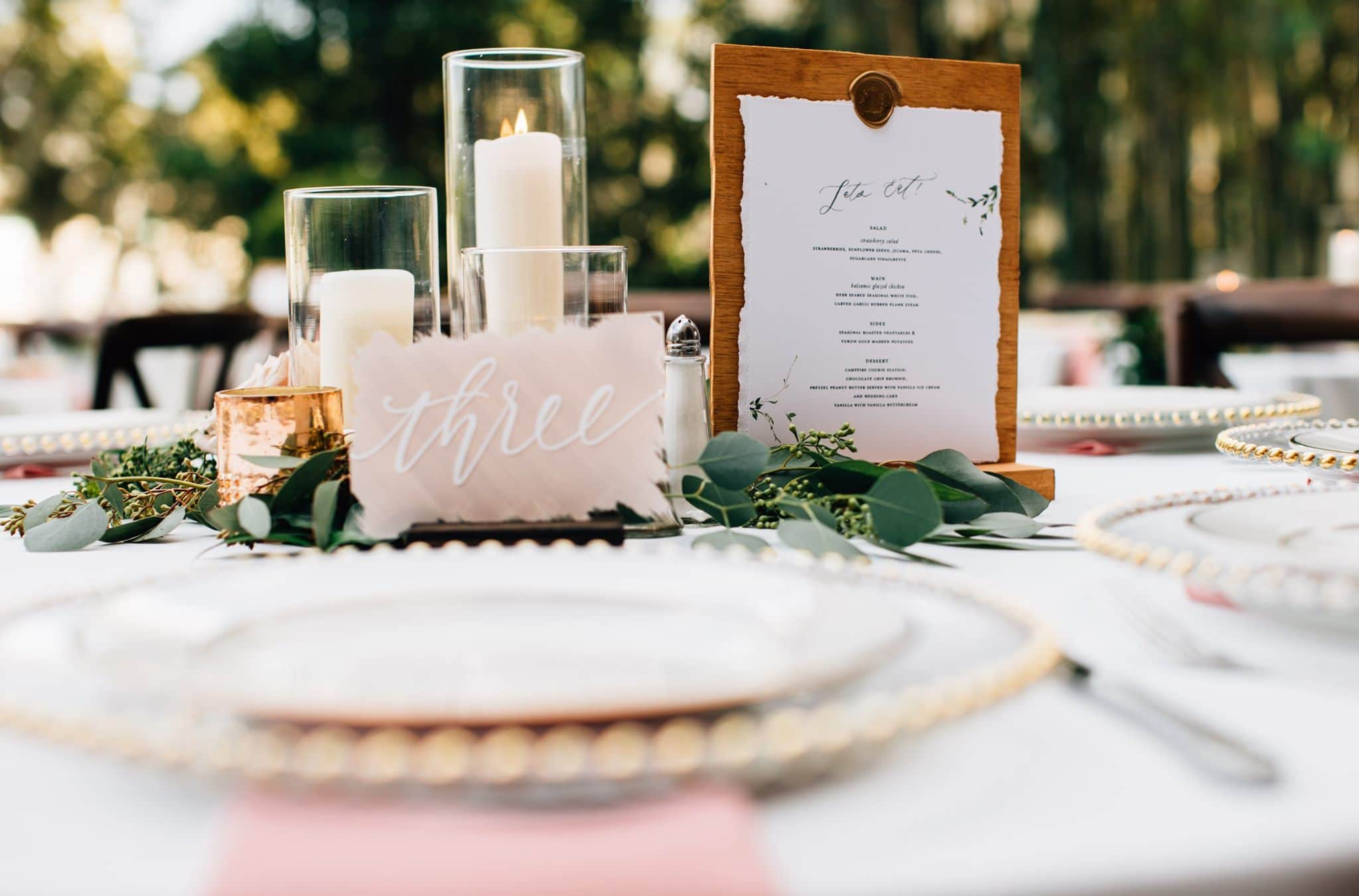 place setting with light pink table number and menu sat up on table with light greenery and candles behind