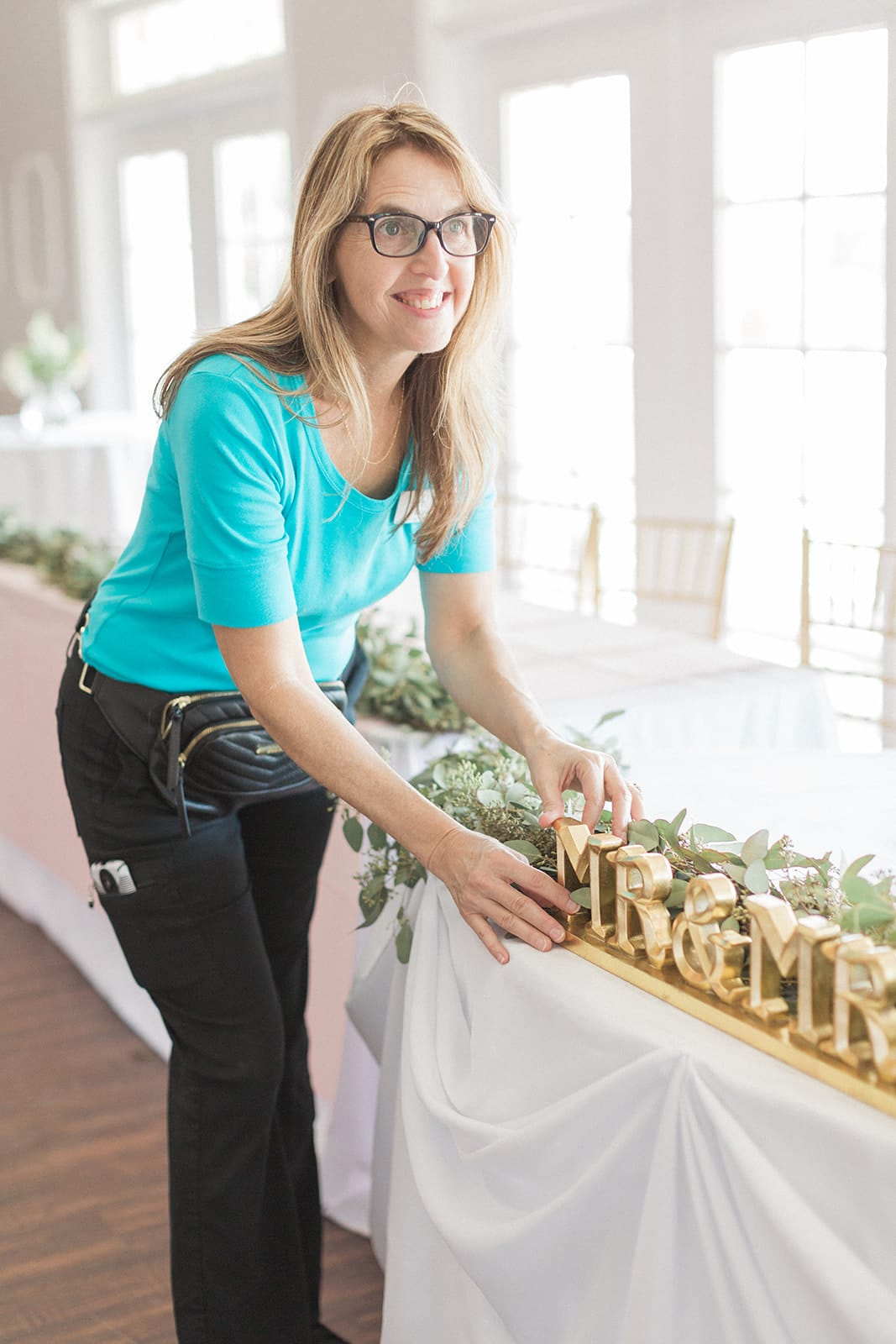 woman wearing glasses black pants teal shirt fixes mr and mrs gold sign on table at wedding while smiling