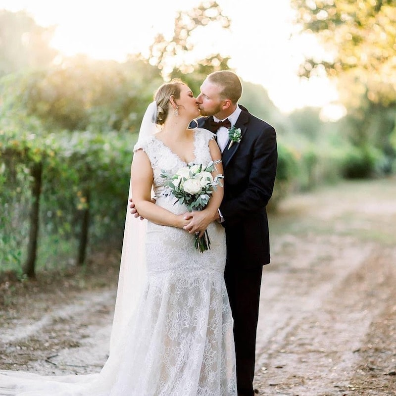 bride and groom kissing while standing on an outdoor path on their wedding day