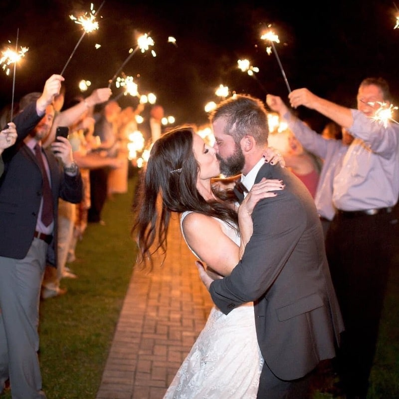 bride and groom kissing during sparkler exit from their wedding reception