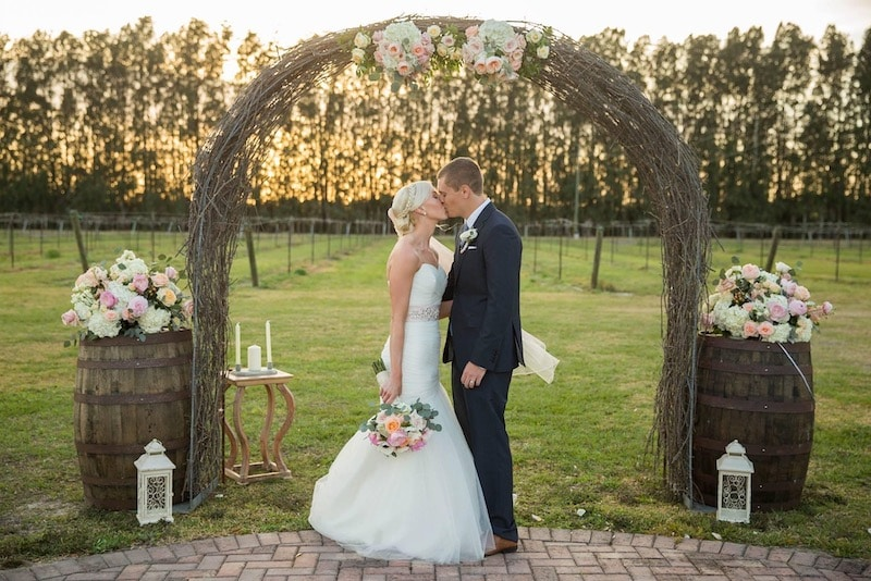bride and groom kissing under an archway on a vineyard at sunset