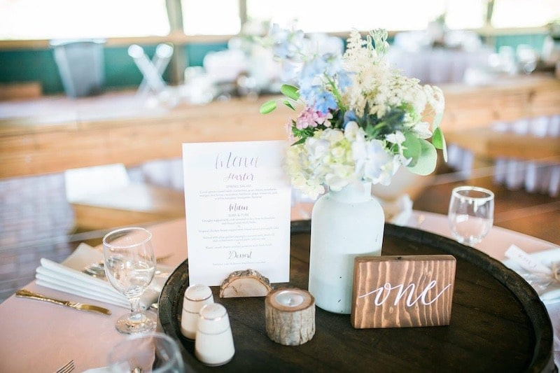 flower centerpiece for wedding reception table featuing wood accents and a personalized dinner menu