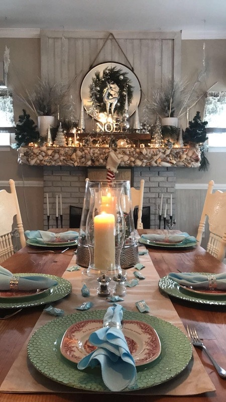 large table setup for dinner at christmastime with christmas decorations on the mantle over the fireplace
