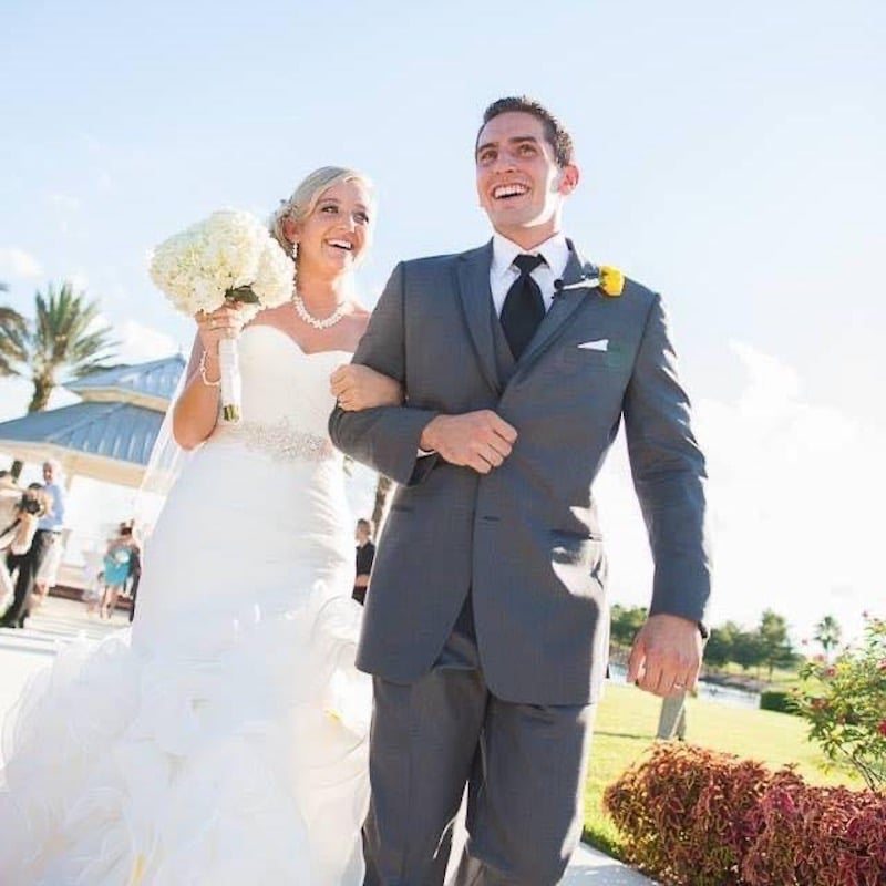 bride and groom walking arm-in-arm and smiling on their wedding day