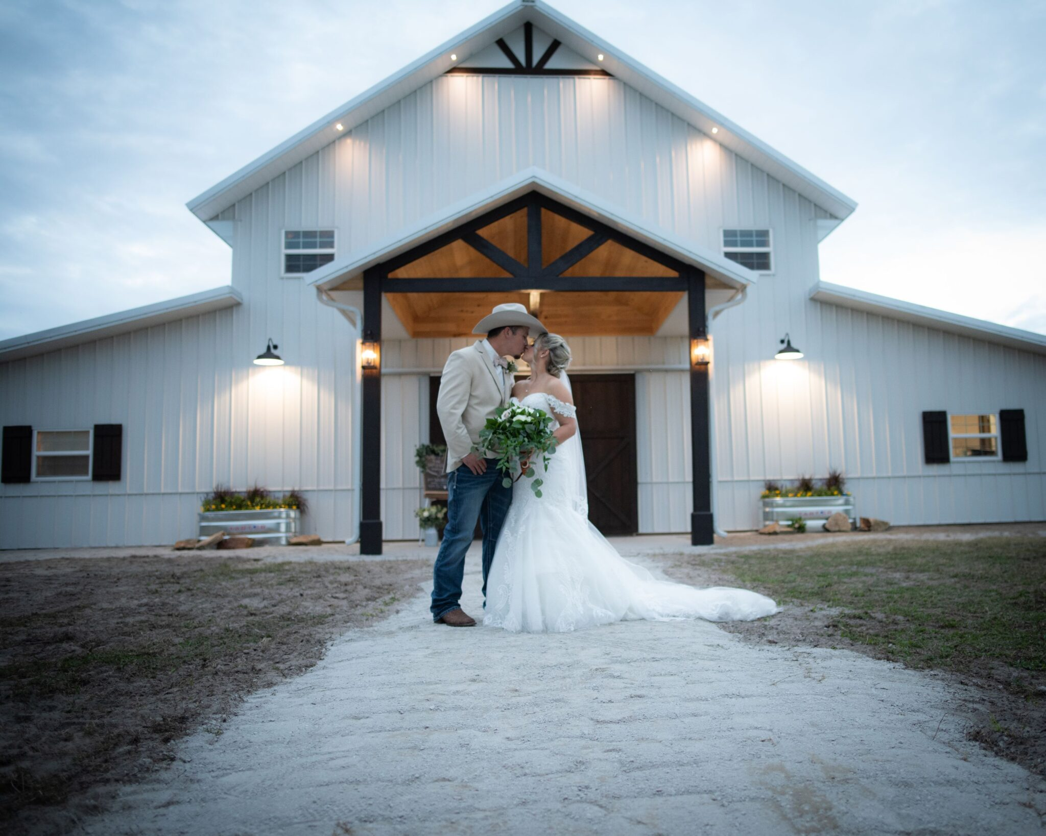 bride and groom kissing in front of large white barn