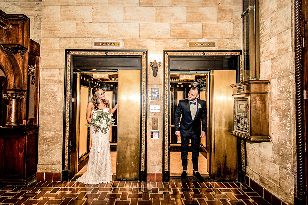 bride and groom getting a first look at each other on their wedding day coming out of separate elevators