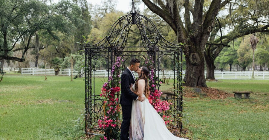 bride and groom kissing outside on their wedding day in front of steel frame gazebo