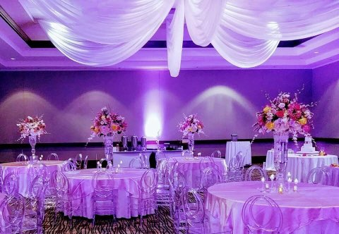 wedding reception set up in ballroom with purple lighting and white drapery hanging from ceiling