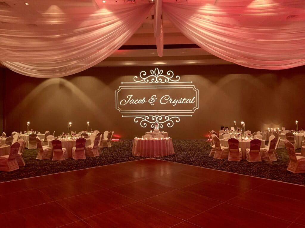 wedding reception in ballroom with large dance floor, drapery hanging from ceiling, and monogram lit on wall