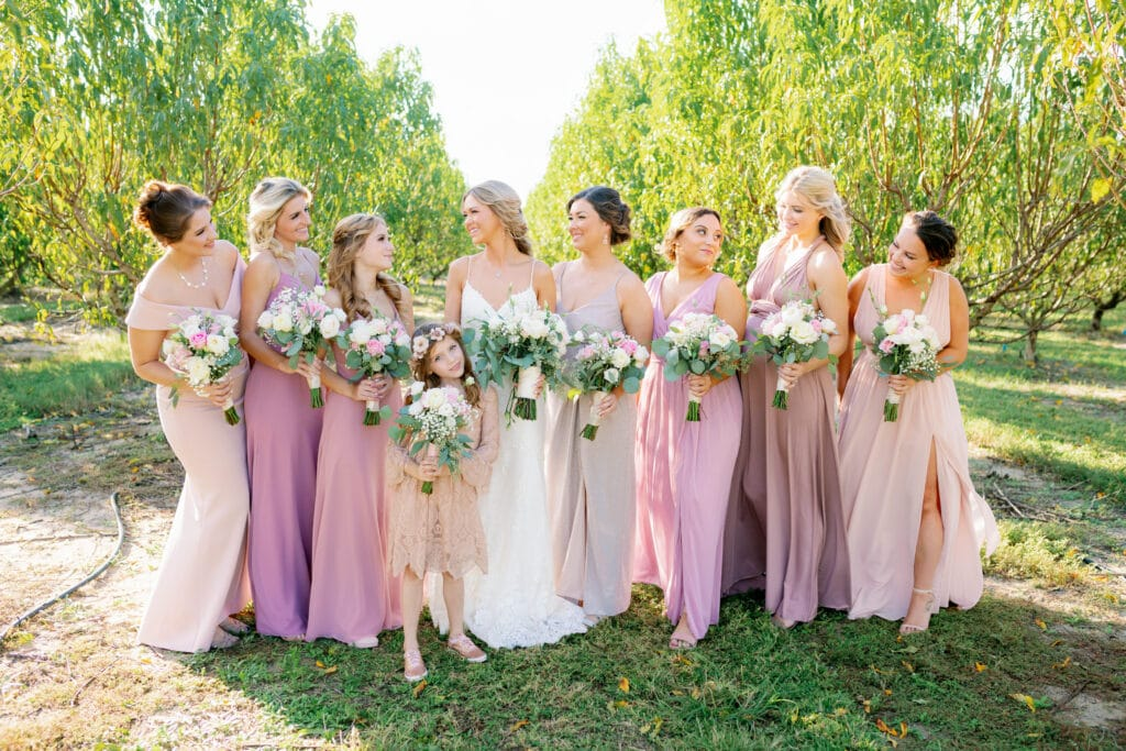bride standing with all of her bridesmaids and flower girl with everyone holding their bouquets
